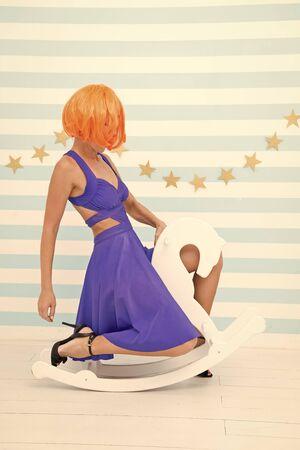 Verrücktes Mädchen in verspielter Stimmung reitet Spielzeugpferd. Werbung im Spielzeugladen. Modemädchen mit orangefarbenem Haar, das Spaß hat. Gemeinsam verrückt werden. Spielzeugladenkonzept mit Frau, die auf weißem Pferd oder Pony spielt