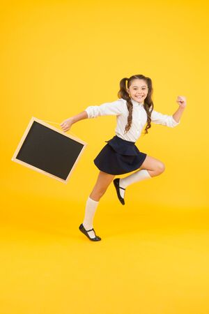 Making step. Schoolgirl pupil informing. School girl hold blank chalkboard copy space. Follow me. Announcement and promotion. Girl school uniform hold blackboard going. Back to school concept