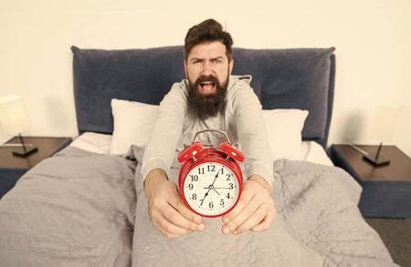 Problem early morning awakening. Get up with alarm clock. Overslept again. Tips for waking up early. Man bearded sleepy face bed with alarm clock in bed. What terrible noise. Turn off that ringing