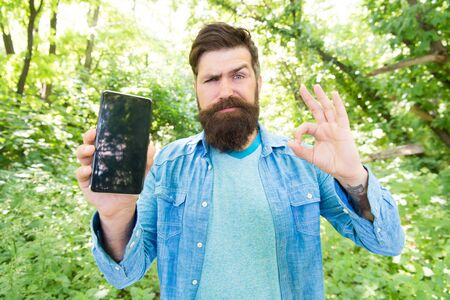 would like wish for best. upset bearded man show ok gesture at phone. Mature hipster with beard. got lost in forest. brutal man with phone. hipster style. guy in forest use gps. summer camping