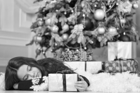 little child girl likes xmas present. Christmas. Kid enjoy the holiday. Happy new year. small sleepy girl at christmas. The morning before Xmas. New year holiday. Santa, please stop