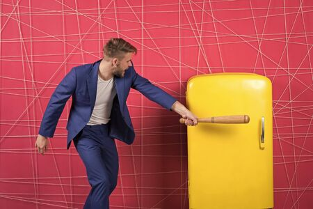 confident businessman in suit. Business fashion. Businessman with bat hit yellow fridge. aggressive man. Feel the success. Male formal fashion. sexy man in stylish jacket. Hungry attack concept