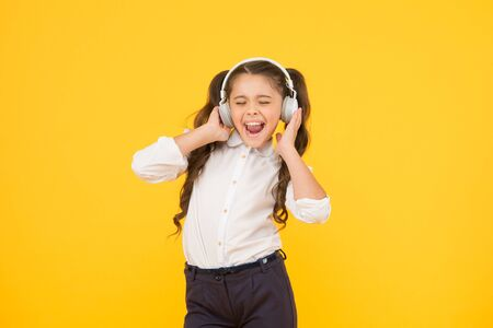 Child enjoy music sound. Audio schooling. Home schooling. Small girl pupil headphones. Child happy listen music. Audio book. Education and fun concept. Online schooling. Listening lesson. Sing song
