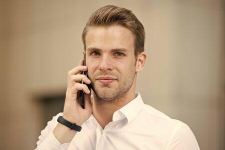 Zapytaj o informacje. Biznesmen dzwoniąc do klienta trzymać smartphone tła miejskiego nieostre. Rozmowa telefoniczna menedżera człowieka. Facet z przyjacielem zadzwoń na smartfona. Koncepcja połączenia komórkowego. Udana rozmowa biznesowa