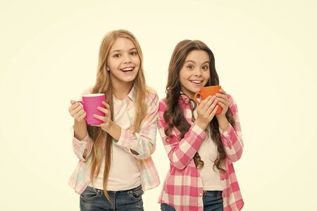 Hot cocoa recipe. Children drink enough during school day. Make sure kids drink enough water. Girls kids hold cups white background. Sisters hold mugs. Drinking tea juice cocoa. Relaxing with drink 写真素材