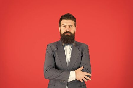 Businessman or host fashionable outfit red background. Formal outfit. Confident posture. Man bearded hipster wear classic suit outfit. Take good care of suit. Elegancy and male style. Fashion concept 版權商用圖片