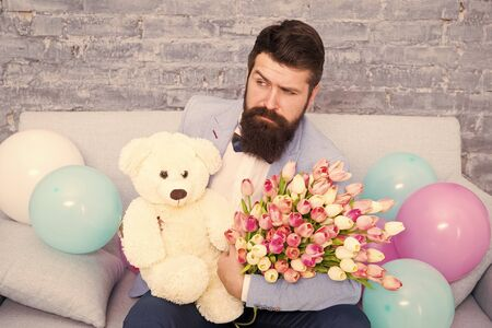 How successfully ask her dating. Romantic gift. Macho ready romantic date. Man wear blue tuxedo bow tie hold flowers bouquet. Romantic man with flowers and teddy bear sit on couch waiting girlfriend Banco de Imagens