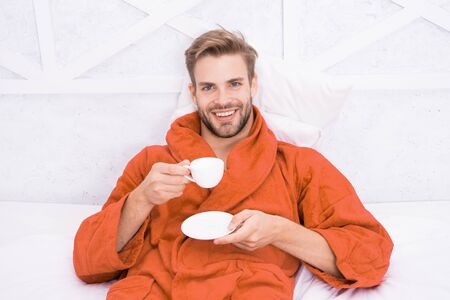 Enjoy morning coffee. Happy morning. Handsome man drink morning coffee. Happy bearded man in bed. Good mood. Starting day with good coffee. Relaxing at home. Pleasant moments. Gourmet espresso Stock Photo