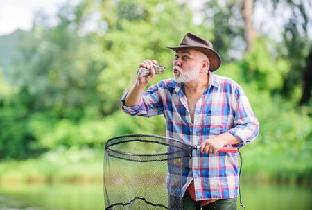 fishing lover. mature man fishing. retired bearded fisher. big game fishing. sport activity and hobby. Trout bait. pothunter. man catching fish. summer weekend. fisherman with fishing rod