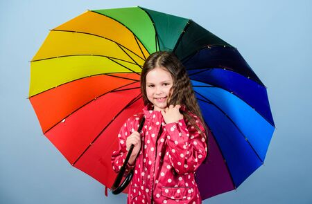 rain protection. Rainbow. happy small girl with colorful umbrella. autumn fashion. Small girl in raincoat. cheerful hipster child in positive mood. Feeling great