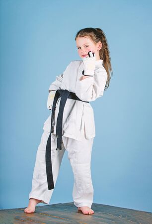 little girl in gi sportswear. practicing Kung Fu. happy childhood. sport success in single combat. small girl in martial arts uniform. knockout. energy and activity for kids. Energy inside
