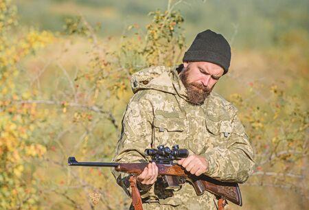 Uomo che mira allo sfondo della natura di destinazione. Fucile da cacciatore. Abilità di mira. Permesso di caccia. Il cacciatore barbuto trascorre il tempo libero a caccia. Attrezzatura da caccia per professionisti. La caccia è un brutale hobby maschile