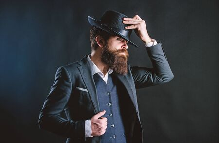Man with hat. Vintage fashion. Man well groomed bearded gentleman on dark background. Male fashion and menswear. Retro fashion hat. Formal suit classic style outfit. Elegant and stylish hipster