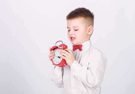 Kid adorable boy white shirt red bow tie. Develop self discipline. Set up alarm clock. Child little boy hold red clock. It is time. Schedule and timing. Morning routine. Schoolboy with alarm clock