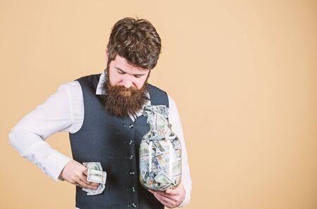 Stuffing some cash into his pockets. Bearded man hiding away cash holdings. Businessman taking cash money out of glass jar. Cash flow budget, copy space