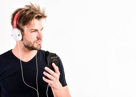 Time stops with nice music. new technology in modern life. sexy muscular man listen music. man listen new song isolated on white. unshaven man in blue tooth technology earphones. moder life concept