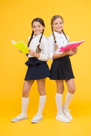 School friendship. Girl with copy books or workbooks. Study together. Kids cute students. Schoolgirls best friends excellent pupils. Schoolgirls wear school uniform. Knowledge day. School day Banque d'images