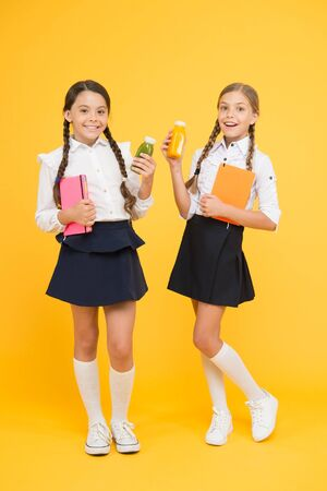 Thirst and dehydration. Healthy snack fruit smoothie. Smoothie detox. Yummy smoothie. Healthy nutrition. Schoolgirls holding juice bottle on yellow background. Quenching thirst during school time Banque d'images