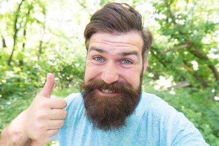 Er gibt seinem Friseur einen Daumen nach oben. Glücklicher Friseur, der auf Naturlandschaft gestikuliert. Bärtiger Mann mit geformtem Bart und Schnurrbarthaar, der vor oder nach dem Besuch des Friseurs lächelt. Ein Friseurladen nur für Männer
