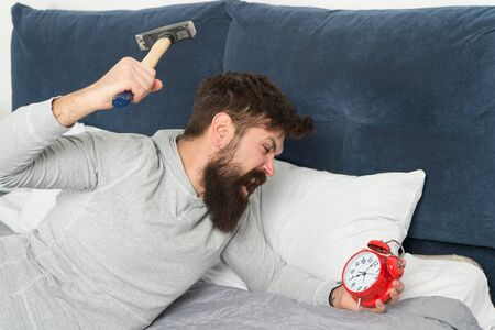 Catch up on missed sleep during weekend. Morning awakening. Stages of sleep. Man awake unhappy with alarm clock ringing. Although you are asleep you may wake up feeling like did not sleep at all 写真素材