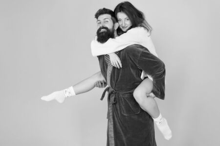 Lets stay at home and have fun. Couple in bathrobes having fun turquoise background. They always have fun together. Close relationship. Handsome young man giving his girlfriend piggyback ride Banco de Imagens