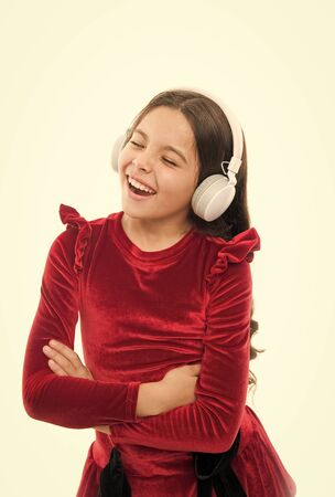 Searching for favorite music. happy childrens day. small girl in red dress. kid fashion and beauty. small child in headphones. music. listening ebook. audio education. childhood and happiness