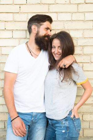 Just hang out together. Couple in love. Family couple hugging on brick wall background. Bearded man and sexy woman cuddling. Sensual couple together. Family day. Careful hug of loving people Banco de Imagens