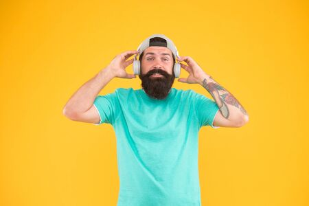 Headset with ergonomic design. Hipster wearing adjustable white headset on yellow background. Bearded man listening to music in stereo headset. Caucasian guy using wireless bluetooth headset