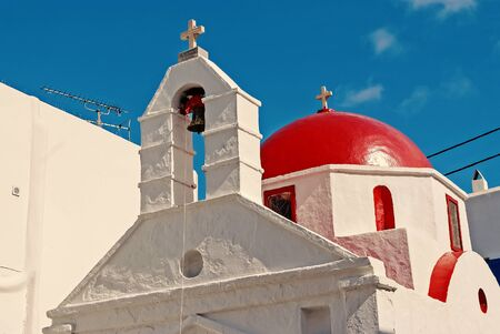 White church architecture in Mykonos, Greece. Chapel with bell tower and red dome. Church building on blue sky. Summer vacation on mediterranean island. Religion and cult concept