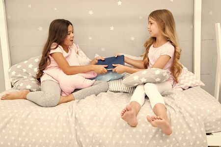 Sisters rivalry concept. Sisters relations issues. Share book with friend. Children in bedroom want read evening fairy tale. This is my book. Girlish rivalry. She dont want to share her book Stock Photo