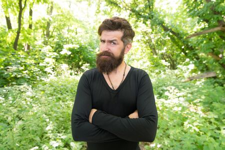 His beard style looks great. Brutal hipster wearing fashionable mustache and beard hair style. Bearded man keeping arms crossed in casual style on summer day. There is style for every man