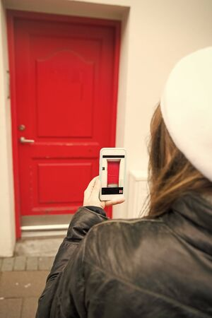 woman take a picture of red door on smartphone outside. digital age and facade design. photo of door on phone. navigation and locations. red point. this would be my home. i like it. Stockfoto