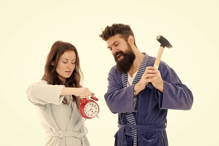 Lets get rid of this annoying alarm clock. Couple in bathrobes going to destroy alarm clock and stay at home. Breaking rules. Tired of early awakening. Man with hammer beat alarm clock. Hateful sound