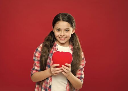 Me to you. Girl cute child hold heart symbol love. Celebrate valentines day. Love and romantic feelings concept. Red heart attribute of valentine. Heart gift or present. Greeting from sincere heart