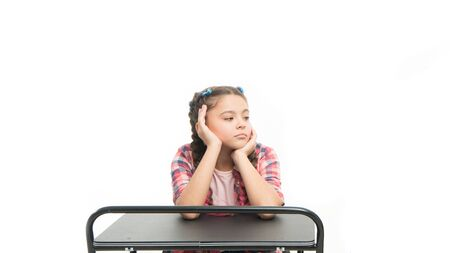 Student seems bored. Uninterested student isolated on white. Small girl student sitting at desk. Little student having lesson in school class