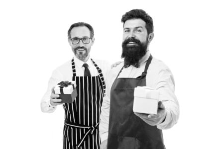 Pleasant gift sweetheart. Surprise her. Prepare surprise dinner. Household service. Men bearded hipster apron hold gift box. Surprise for spouse. Take care of her. Share household responsibilities Banco de Imagens