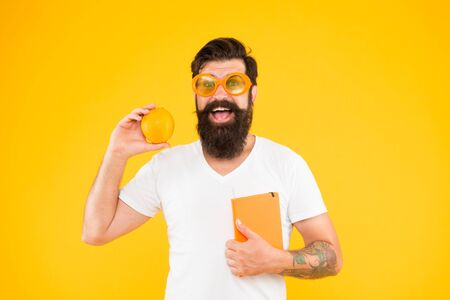 Nerd is the new cool. Bearded nerd man. Study nerd holding book and orange fruit on yellow background. Book nerd in fancy glasses choosing natural diet