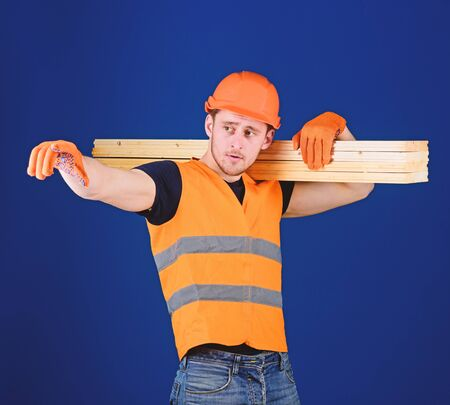 Man in helmet, hard hat and protective gloves pointing direction, blue background. Carpenter, woodworker, strong builder on thoughtful face carries wooden beam on shoulder. Wooden materials concept Banque d'images - 128883389