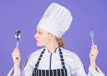 Woman chef hold utensil spoon fork. Appetite and taste. Traditional culinary meal. Professional cook and cooking at home. Tasty homemade food. Time to try meal. She is hungry. Enjoy your meal Archivio Fotografico