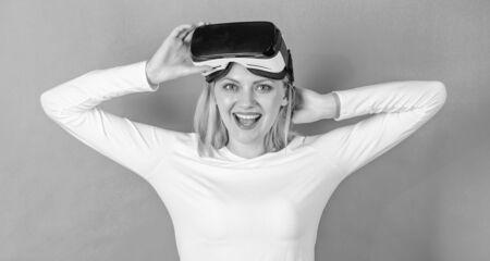 Beautiful woman wearing virtual reality goggles in studio. Woman using virtual reality headset. Woman enjoying cyber fun experience in vr. Tech vision.
