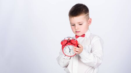 Party time. Businessman. Formal wear. little boy with alarm clock. Time to relax. Time management. Morning. tuxedo kid. Happy childhood. happy child with retro clock in tie. copy space. Just relaxing Stockfoto - 128882814