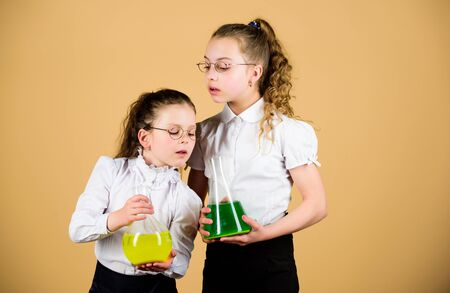 little smart girls with testing flask. back to school. knowledge and education. children study at biology lesson. science research in lab. chemistry flask with liquid. testing flask in hands of kids Archivio Fotografico