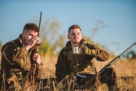 Rest for real men concept. Hunters with rifles relaxing in nature environment. Hunters friends enjoy leisure. Hunting with friends hobby leisure. Hunters satisfied with catch drink warming beverage