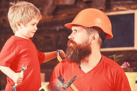Father, parent with beard in protective helmet teaching little son to use different tools in school workshop. Fatherhood concept. Boy, child cheerful holds spanner wrench, learning use tools with dad Banco de Imagens