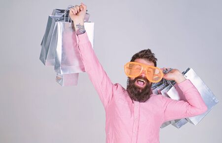 Stupid things you do with your money. How to stop buying things you dont need. Obsessed with shopping. Addicted consumer concept. Man bearded hold shopping bags. Shopping dumb wasting money