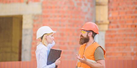 Safety inspector concept. Construction site safety inspection. Discuss progress project. Woman inspector and bearded brutal builder discuss construction progress. Construction project inspecting