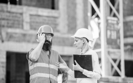 Safety inspector concept. Inspector and bearded brutal builder discuss construction progress. Construction project inspecting. Construction inspection, corrections and fines. Discuss progress project Stock Photo