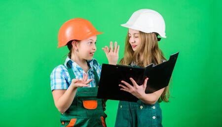 small girls repairing together in workshop. Labor day. 1 may. school project. Happy children. Little kids in helmet. Foreman inspector. Repair. repairing house together. kids repairing together Imagens