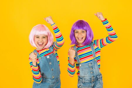 Anime convention. Anime cosplay party concept. Animation style characterized colorful graphics vibrant characters fantastical themes. Happy little girls. Anime fan. Cheerful friends in colorful wigs Stock Photo