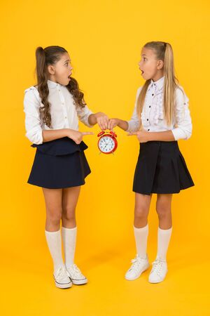 Schoolgirls and alarm clock. Children school pupils. Knowledge day. School time. Surprised shocked kids hold alarm clock counting time. Latecomer will be punished. It is time. School schedule Imagens